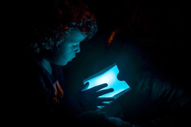 Close-up of boy holding illuminated light in darkroom