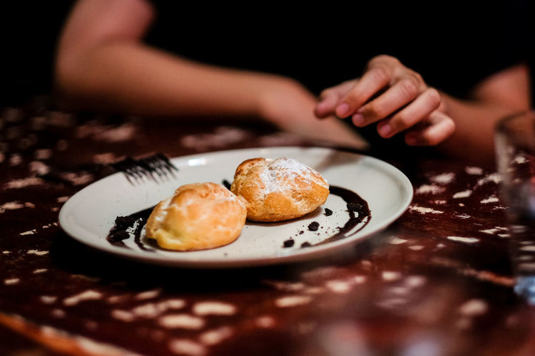 Tempting to eat the cream puff Food And Drink Food Indoors  Human Hand One Person Freshness Hand Selective Focus Plate Table Real People Human Body Part Sweet Food Ready-to-eat Midsection Close-up Sweet Baked Indulgence Temptation Breakfast Finger