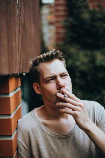 Young Man Smoking Cigarette While Leaning On Brick Wall