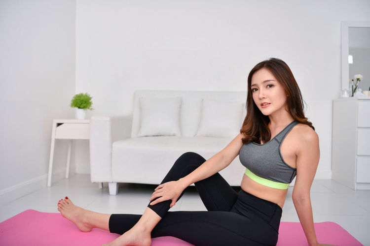 Portrait of beautiful woman practicing yoga at home