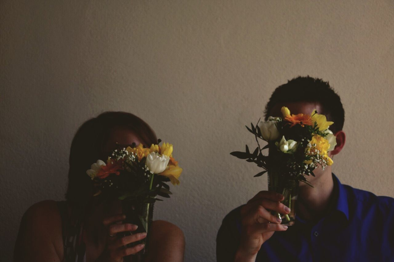 Obscured Friends Faces From Flowers Against Wall