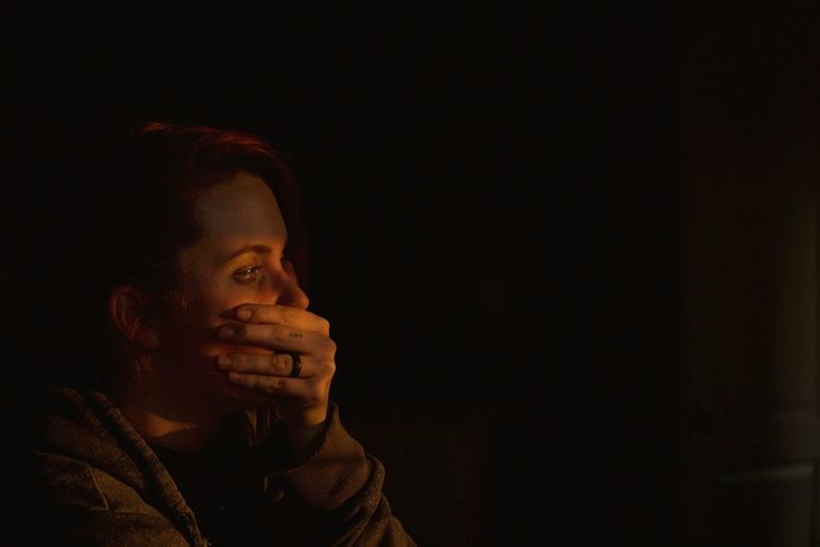 Young woman looking away covering mouth against black background