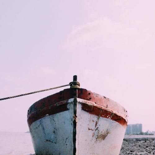 Low angle view of rusty ship on sea against sky
