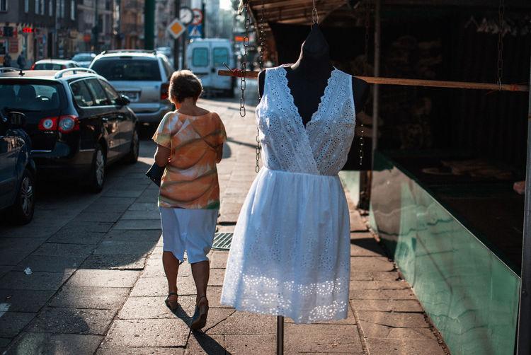 Rear view full length of woman walking by mannequin on sidewalk in city