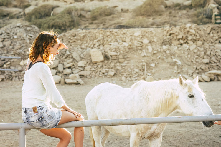 Woman sitting by pony on railing in ranch