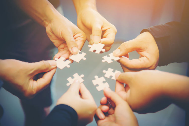 Close-Up Of People Holding Jigsaw Pieces