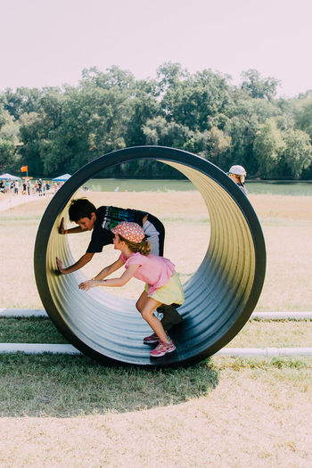 Boy And Girl Playing In Pipe At Park