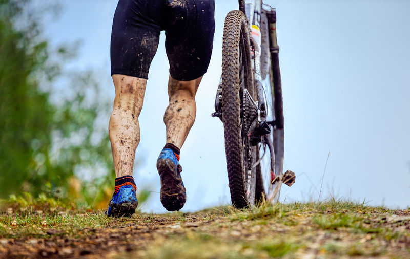 Low section of man with bicycle on dirt road
