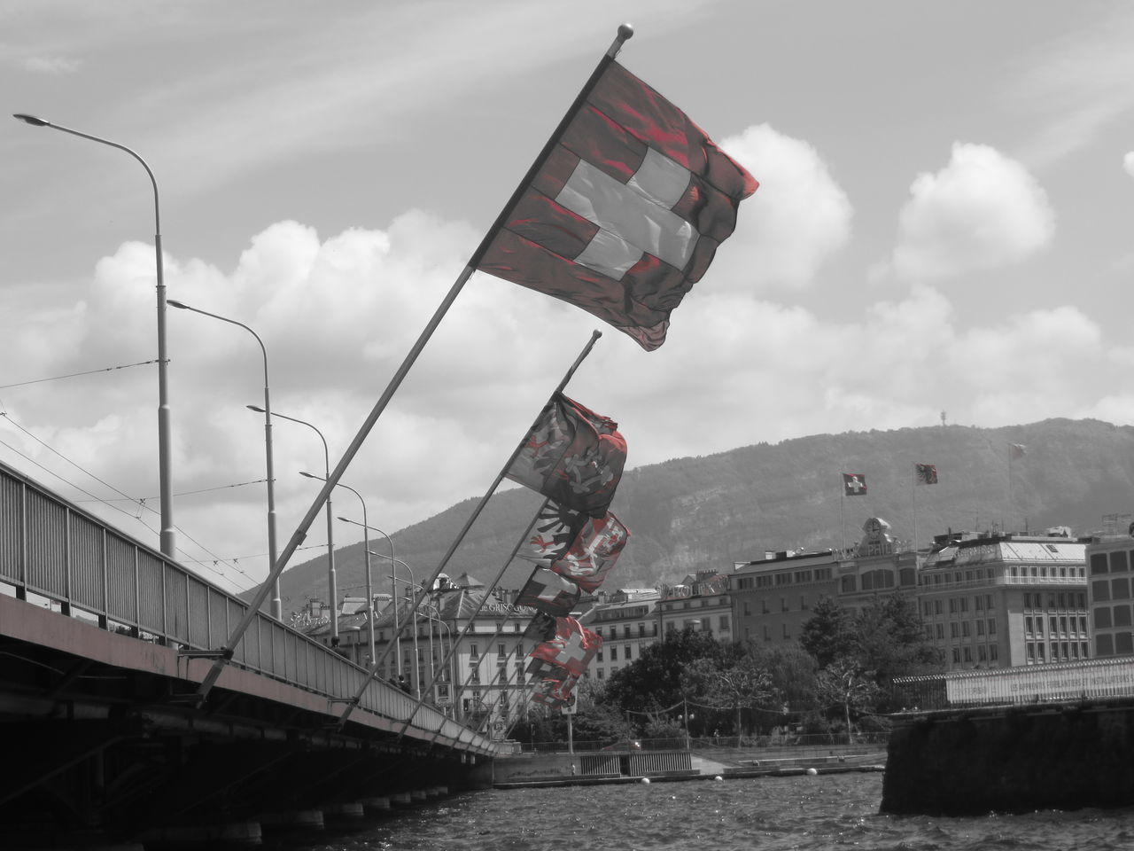 flag, architecture, patriotism, built structure, day, river, water, bridge - man made structure, sky, transportation, cloud - sky, outdoors, waterfront, no people, building exterior, nature, mountain