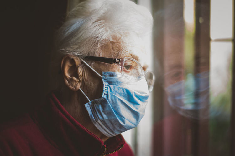 Close-up of senior woman wearing mask with reflection on window