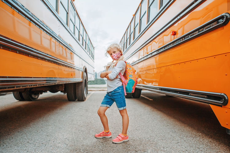 Portrait of girl standing against bus