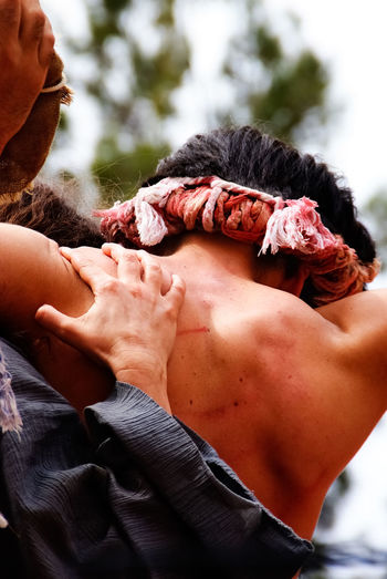 Rear view of people carrying man for crucifix outdoors