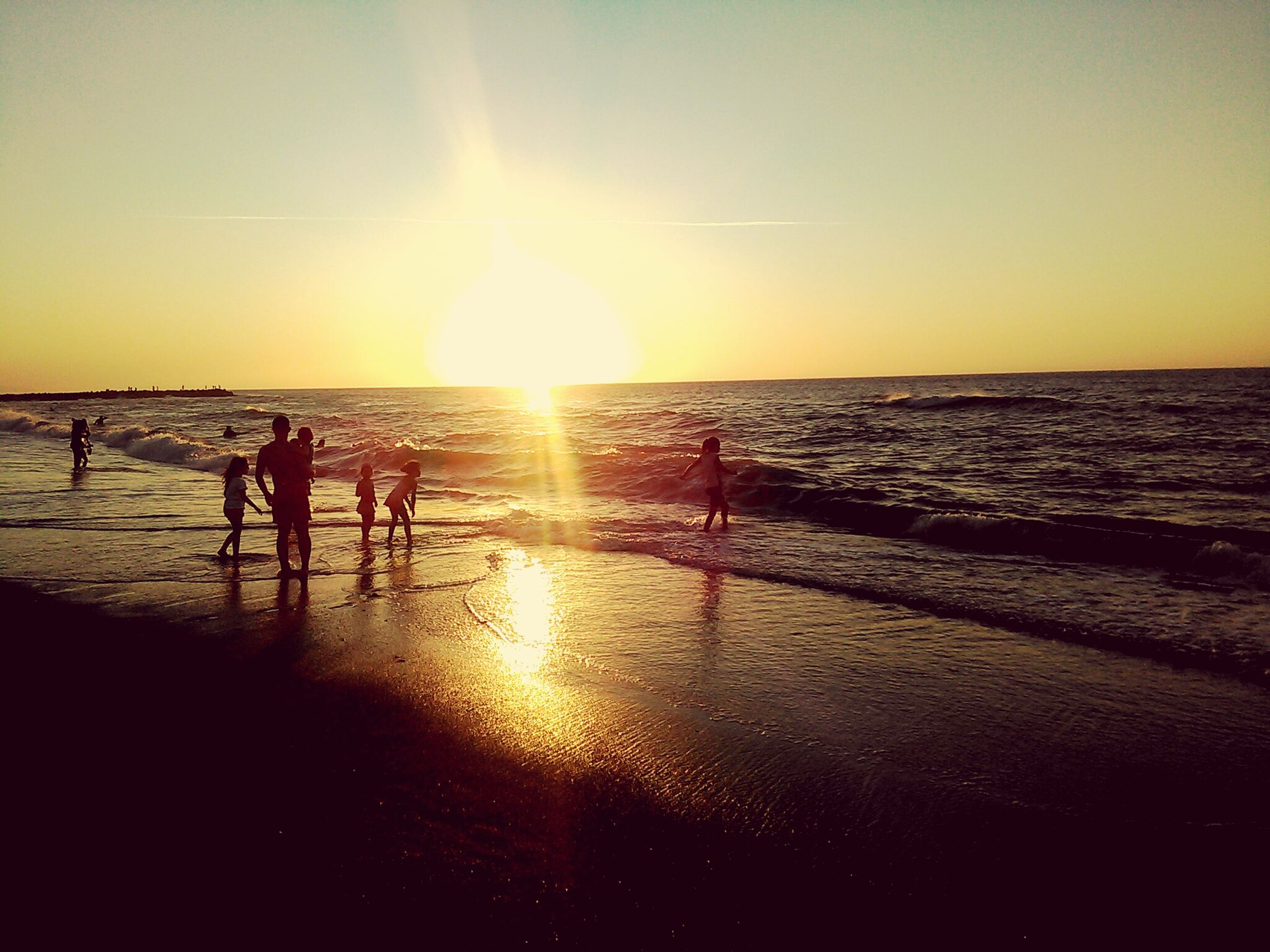 beach, sea, water, sunset, horizon over water, sun, reflection, scenics, shore, silhouette, sunlight, vacations, tranquil scene, tranquility, leisure activity, beauty in nature, lifestyles, sand, orange color, sky, sunbeam, nature, tourist, coastline, calm, majestic, tourism, lens flare, outline, person, summer, outdoors