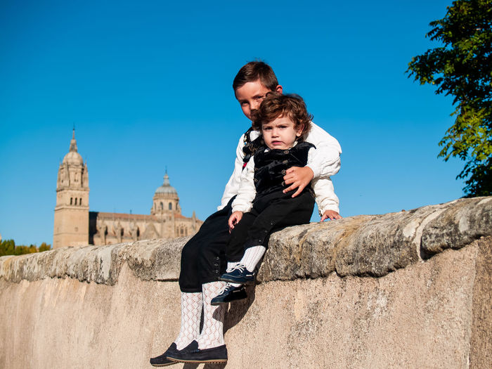 Portrait cute siblings sitting on wall against historic building