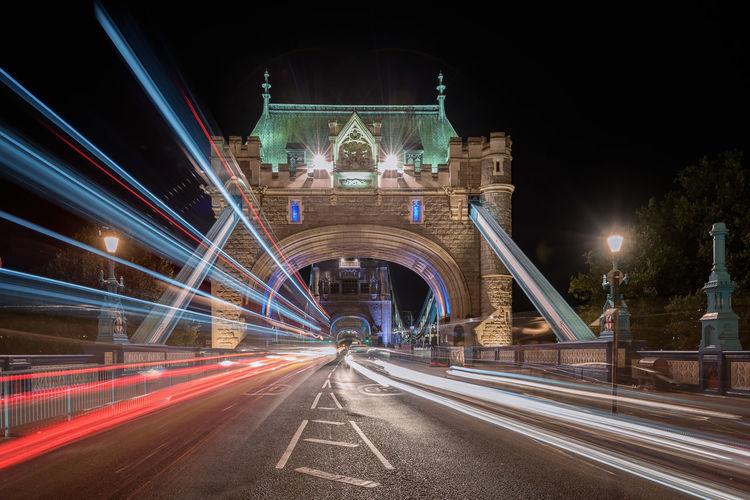 Light trails on tower bridge against sky at night