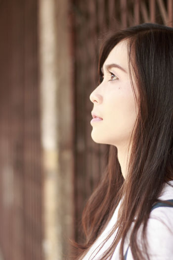 Side View Of Thoughtful Young Woman Standing By Closed Gate