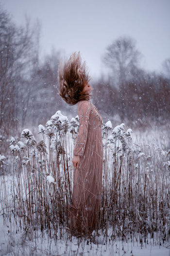 Rear view of woman standing on snow covered field