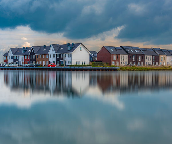 Houses by lake against cloudy sky in city