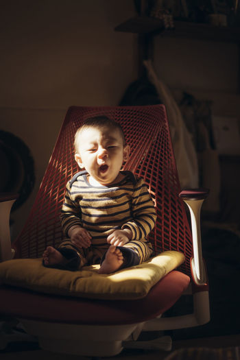 Portrait of cute baby boy yawning while sitting on chair at home
