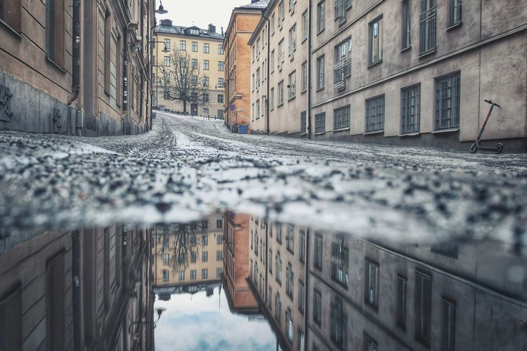 Surface level of puddle on street amidst buildings in city