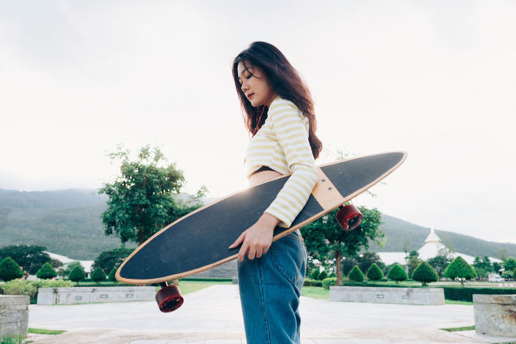 Young woman holding skateboard while standing on street