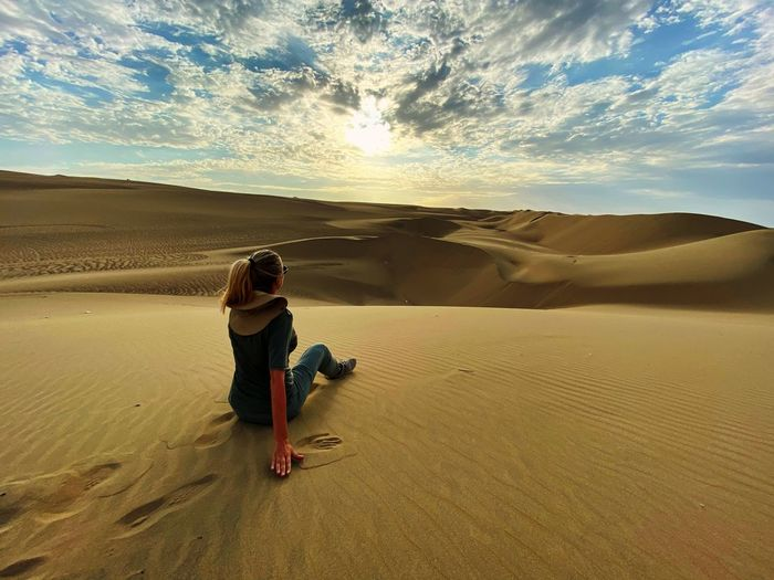 Rear view of woman on sand dune in desert against cloudy sky