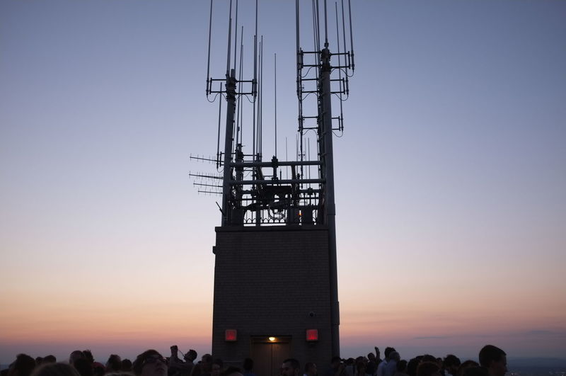 Crowd at observation point against sky during sunset