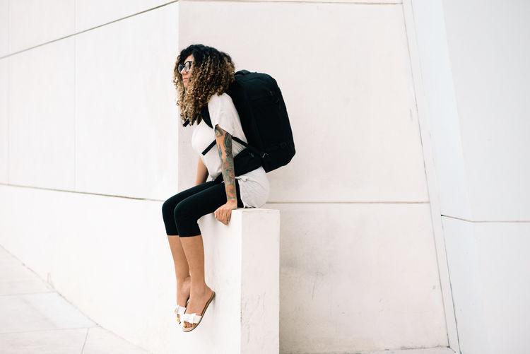 Full length of girl wearing bag sitting against wall