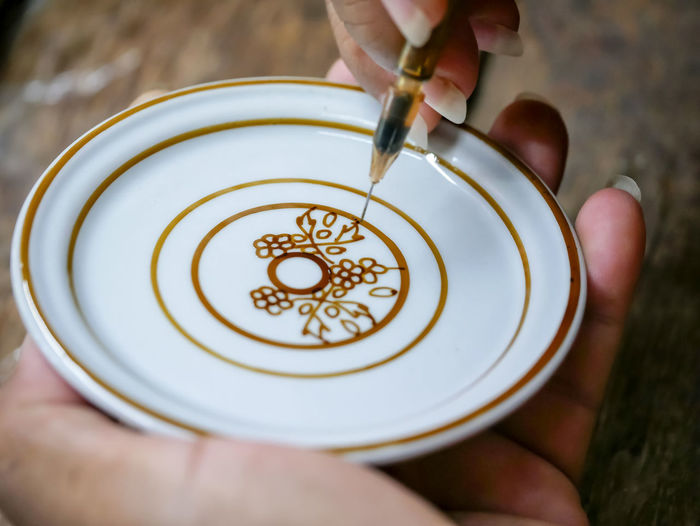 Cropped image of woman making design on saucer