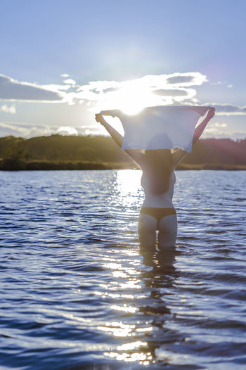 Arms Raised Beauty In Nature Human Arm Leisure Activity Lifestyles Nature One Person Outdoors Real People Reflection Scenics - Nature Sea Sky Sunlight Swimwear Vacations Water Waterfront Women