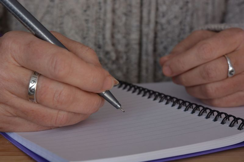 Close-up of person hand holding paper on table