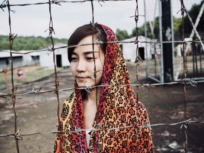 Close-Up Of Young Woman Standing By Chainlink Fence