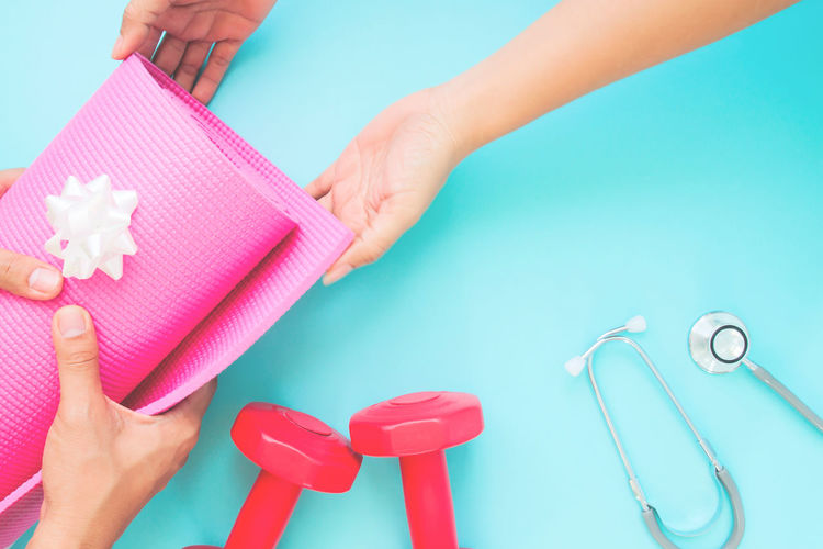 Close-Up Of Hands Giving Exercising Mat To Person By Dumbbells And Stethoscope Over Blue Background