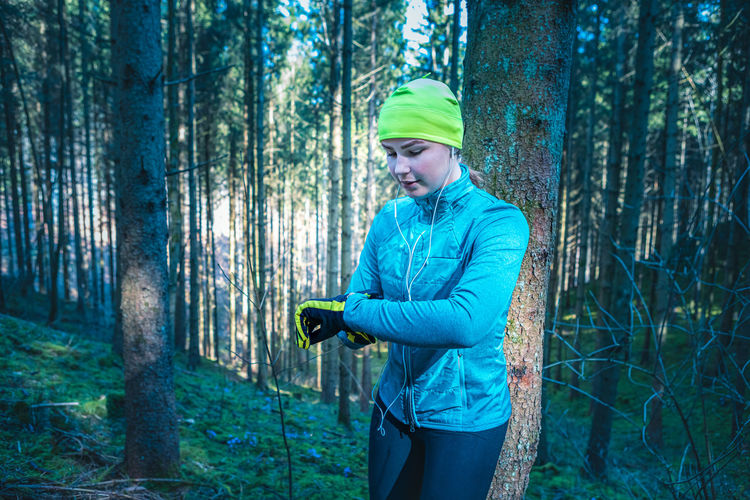 Woman checking time while standing in forest