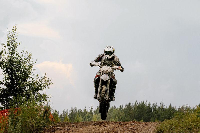 Biker riding motorbike on land against sky