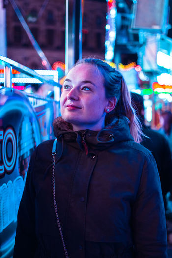 Close-up of young woman standing against illuminated amusement ride at night