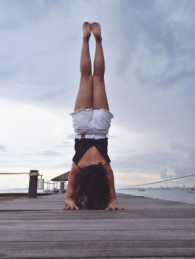 Woman Exercising On Pier Over Sea Against Sky