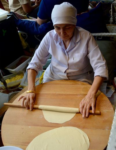 High angle view of senior woman rolling dough on table