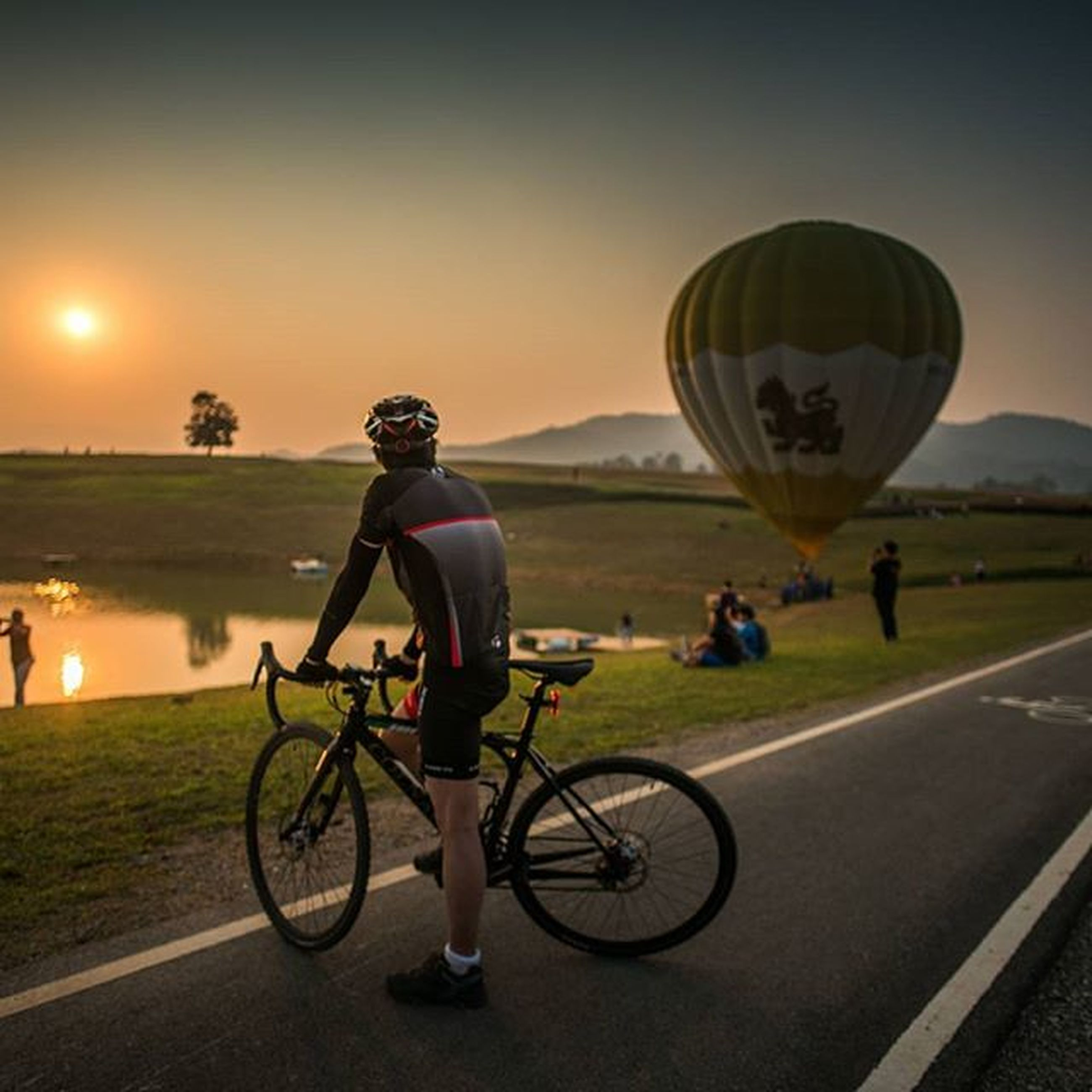 bicycle, transportation, land vehicle, mode of transport, riding, road, cycling, lifestyles, leisure activity, full length, men, street, grass, sky, on the move, travel, sport, road marking