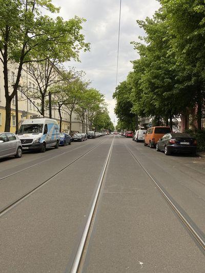 Cars on street in city against sky