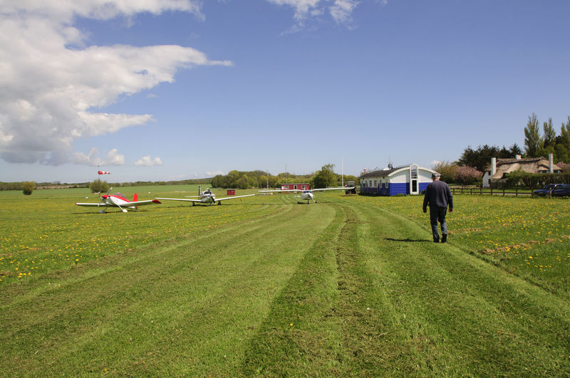 Rear view of man walking on grassy airfield
