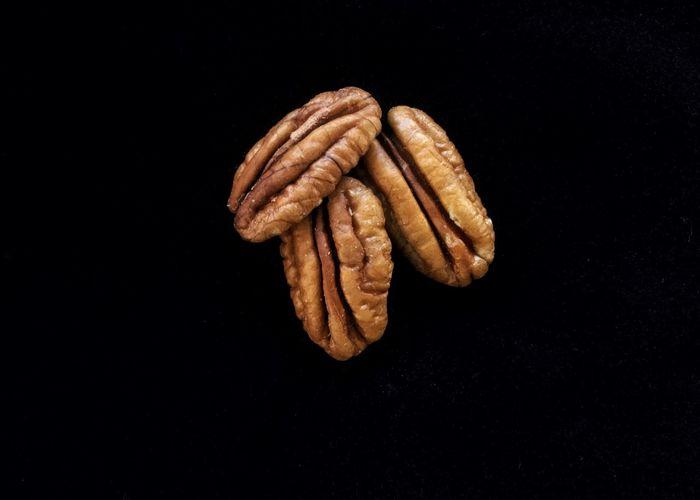 Pecan halves on a black background. Black Background Pecans Pecan Halves Nuts No People Studio Shot Food Close-up Tree Crop Tree Nuts Pecan
