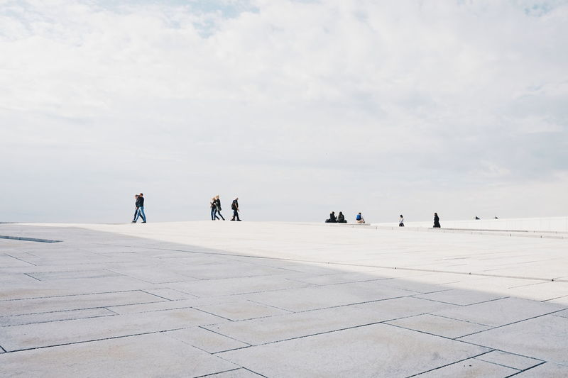 People at oslo opera house against cloudy sky