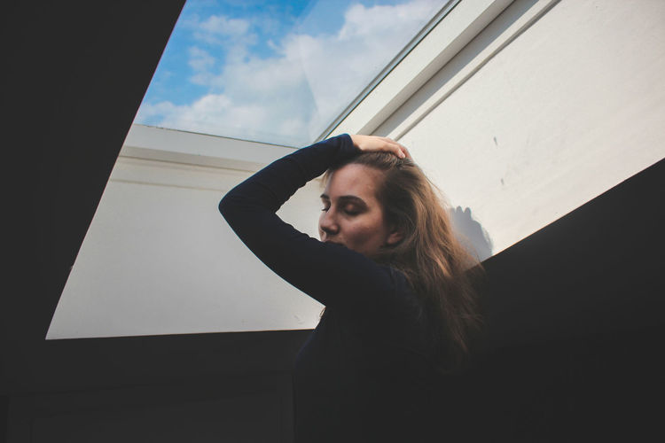 Low angle view of woman standing below skylight