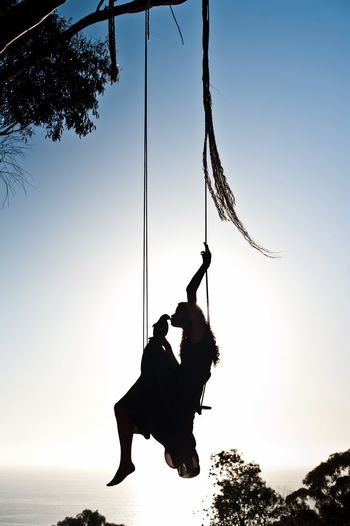 Silhouette of woman kissing bird on swing at sunset