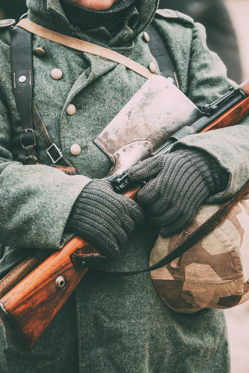 Midsection of soldier holding gun and hat