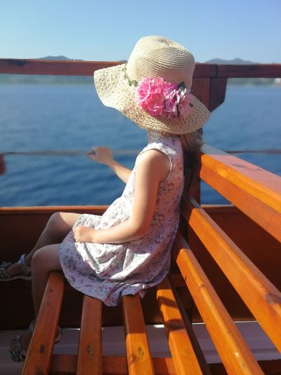 Girl sitting on bench by sea