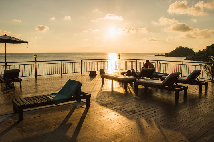 People relaxing on lounge chairs at observation point by sea during sunset