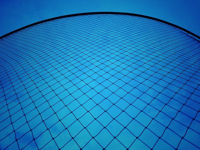 Low angle view of grid pattern against clear blue sky