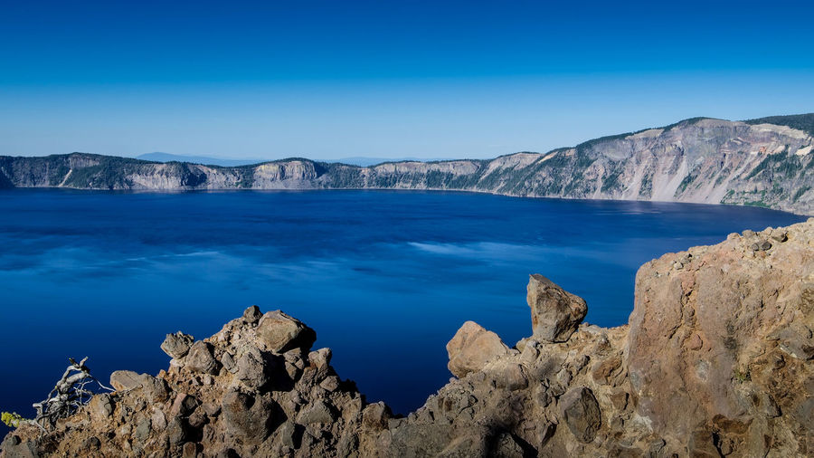 Panoramic view of the East side of blue Crater Lake from the Garfield Trail in the summer during the day, against cloudless, blue sky Blue Sky Rock Scenics - Nature Beauty In Nature Water Tranquil Scene Mountain Solid Tranquility Rock - Object Rock Formation No People Clear Sky Idyllic Formation Volcano Crater Lake Volcanic Crater Volcanic Rock Oregon Urban Skyline Travel Destinations